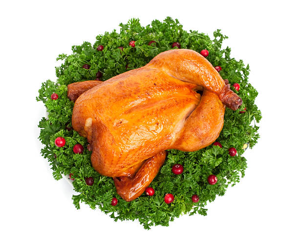 Cooked holiday turkey surround by greens and cranberries stock photo