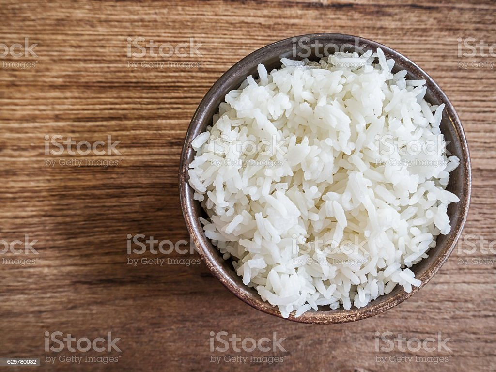 Cooked jasmine rice in a bowl on wooden table stock photo
