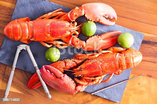 Close up Cooked Red Lobsters Duo on a Gray Cutting Board with Lime and Cracking Tool, on Top of a Wooden Table.
