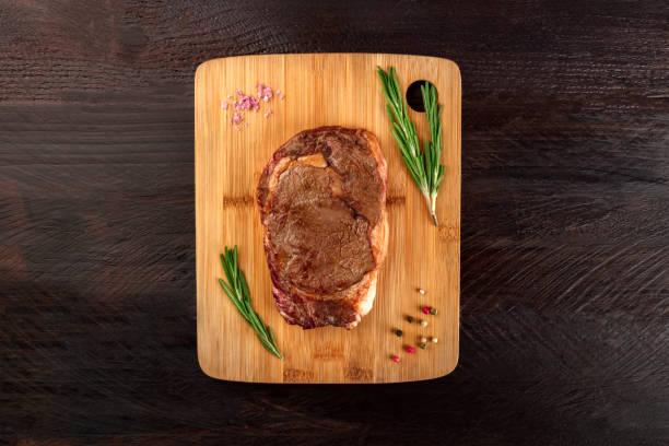 gekochtes fleisch auf rustikalen texturen mit gewürzen und exemplar - steak anbraten stock-fotos und bilder