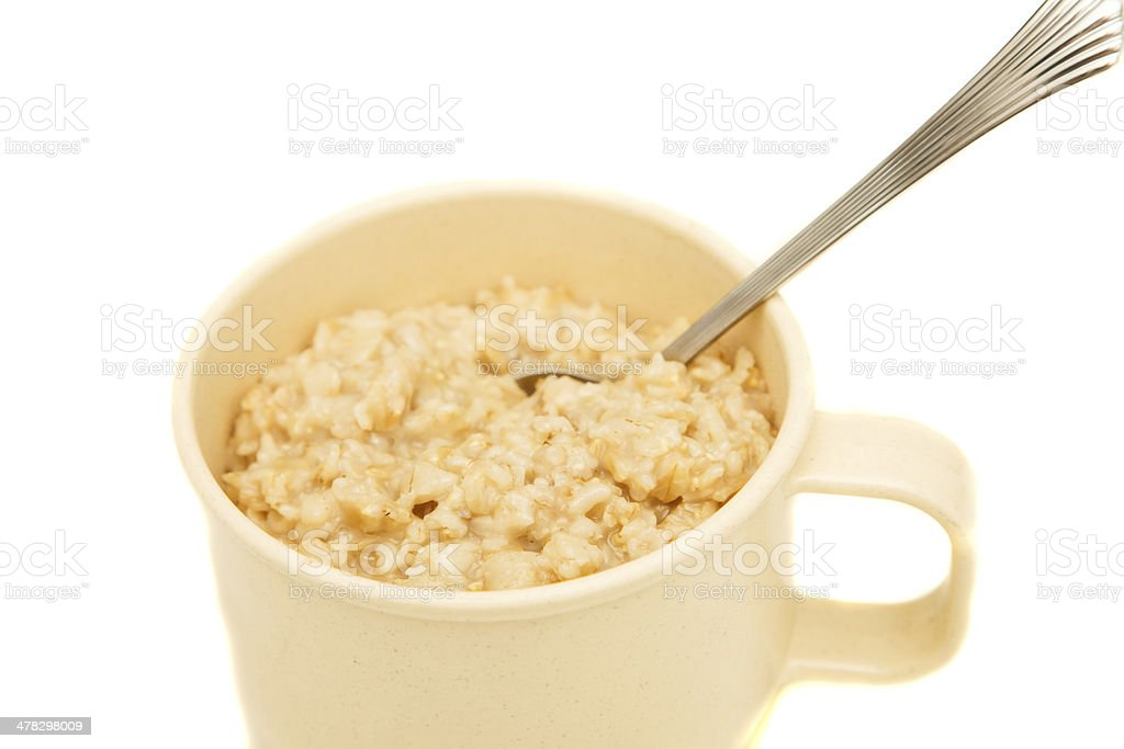Cooked Oatmeal in a Cup with Spoon royalty-free stock photo