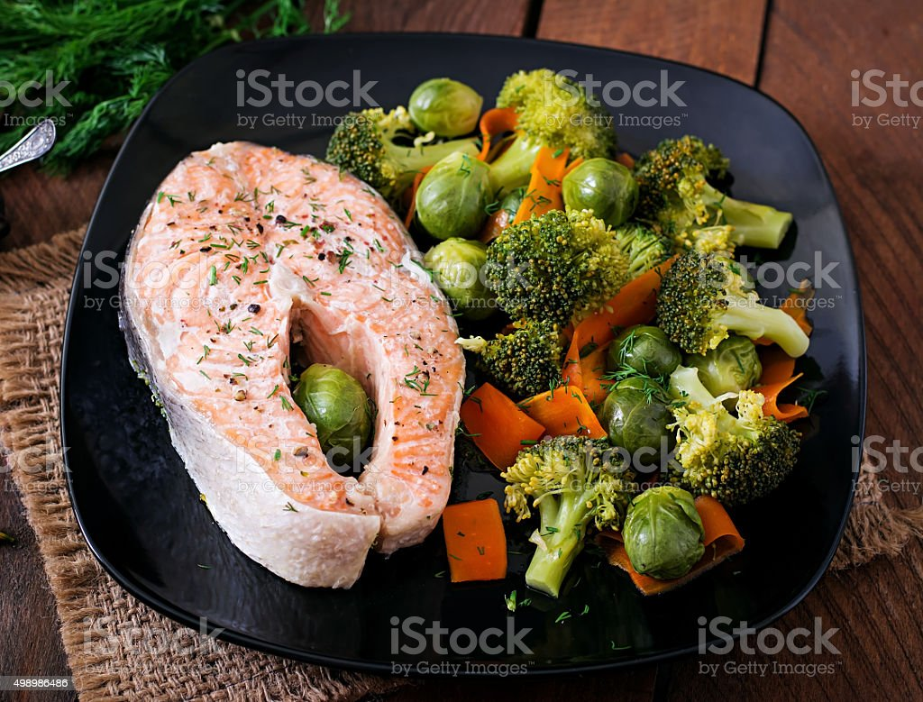 Cooked on steam salmon steak with vegetables. stock photo