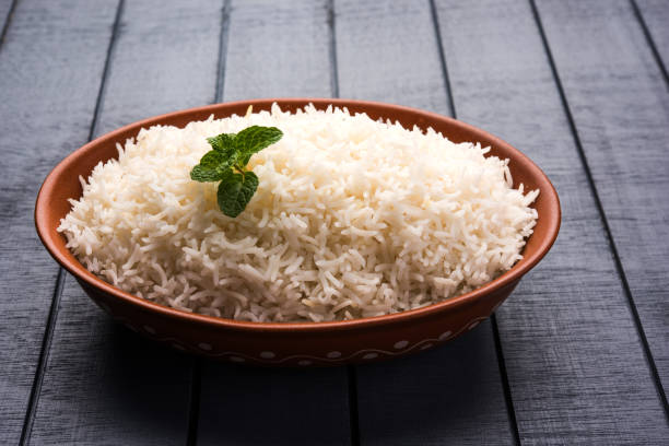 Cooked plain white basmati rice in terracotta bowl over plain or wooden background Cooked plain white basmati rice in terracotta bowl over plain or wooden background basmati rice stock pictures, royalty-free photos & images