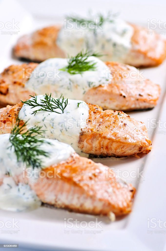 Cooked salmon steaks with sauce and dill garnish royalty-free stock photo