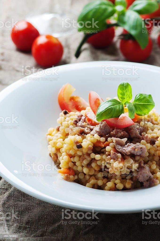 Cooked sardinain pasta fregola with tomato and sausage stock photo