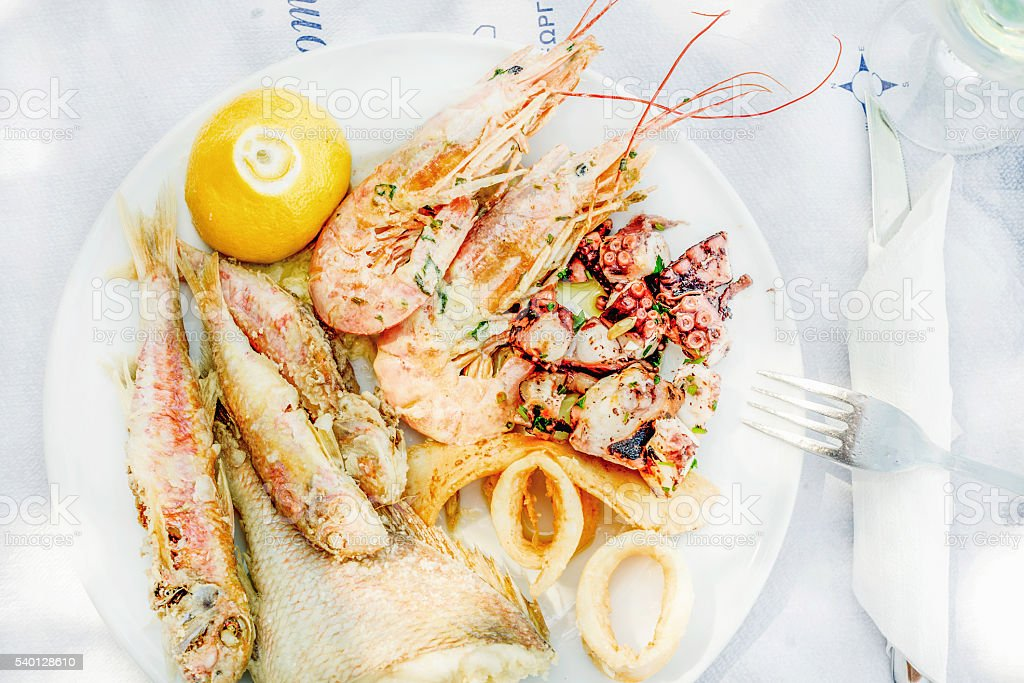 Cooked seafood on plate with lemon and wine Cooked seafood on plate with lemon and wine. Prawns, squid, octopus, mullet fish and seabream. Traditional Mediterranean dish on Greek island of Kastelorizo Calamari Stock Photo