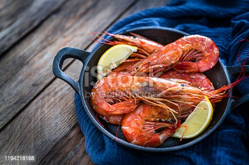 Seafood: high angle view of fresh shrimps in a cast iron cooking pan shot on rustic wooden table. Predominant colors are red, blue and brown. High resolution 42Mp studio digital capture taken with Sony A7rii and Sony FE 90mm f2.8 macro G OSS lens