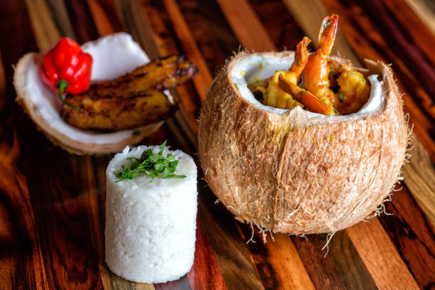 cooked shrimp in a coconut bowl, white rice, cilantro, friend plantains and red habanero oven a wood texture - caribbean culture stock pictures, royalty-free photos & images