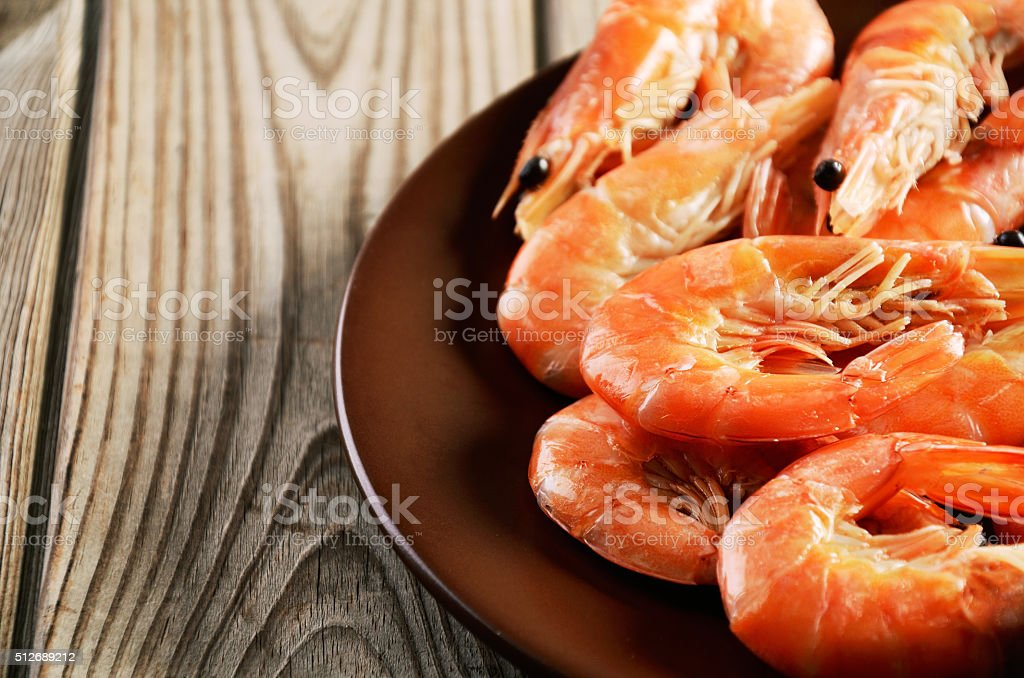 cooked shrimp on  plate a wooden background close-up stock photo