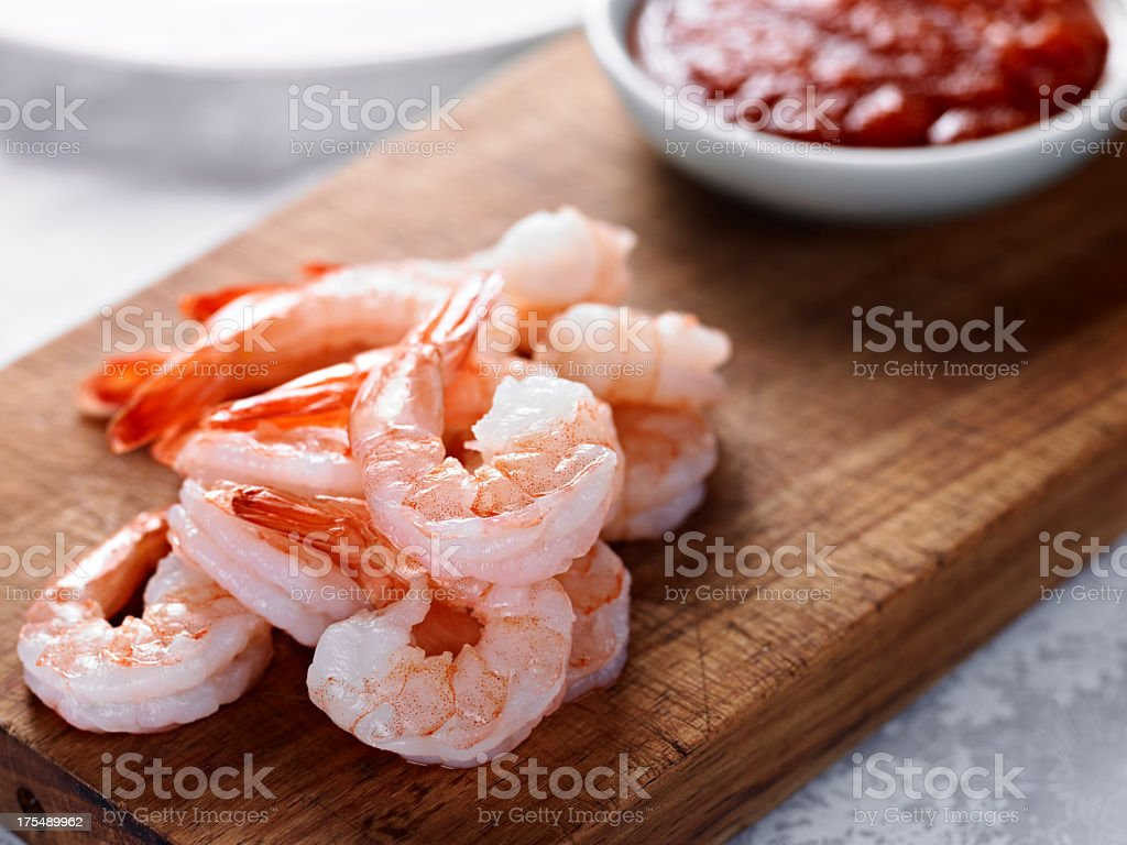 Cooked shrimps on wooden board next to red sauce stock photo