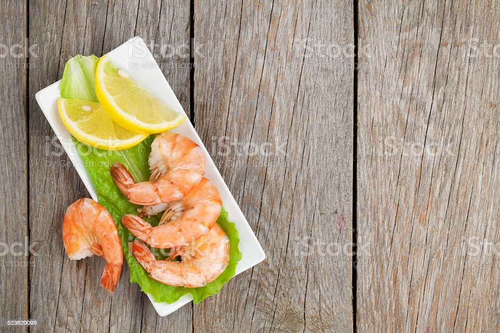 Cooked shrimps with lemon and salad leaves stock photo