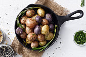Cooked three colors small potatoes in a cast iron skillet on a white background