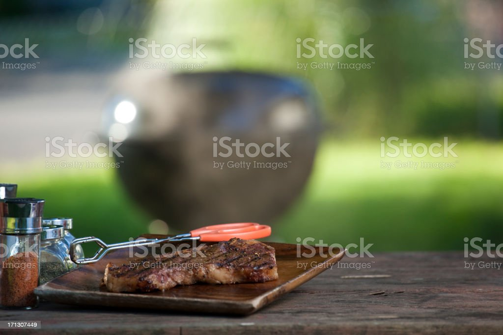 Cooked steak on a wooden board with grill in background stock photo