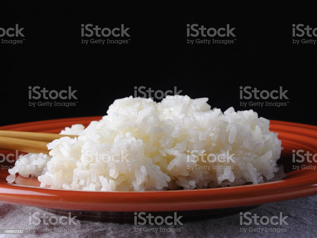 Cooked, Sticky Rice on an Orange Plate with Chopsticks stock photo