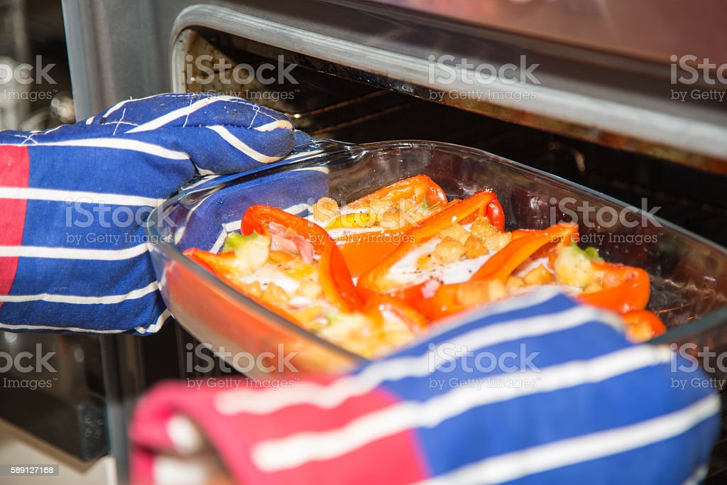 Cooked stuffed red peppers with eggs, ham and croutons. stock photo