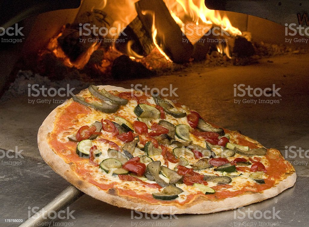Cooked Traditional Italian Vegetarian Pizza comming out of the Oven stock photo