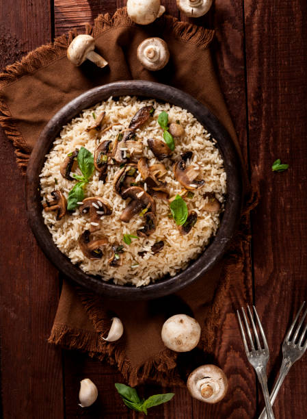 Cooked white rice with mushroomsin a bowl on wooden background. Cooked white rice with mushrooms in a bowl on wooden background. Top view with copy space. basmati rice stock pictures, royalty-free photos & images