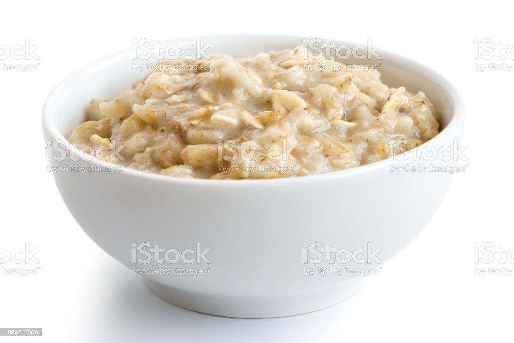 Cooked whole porridge oats in white ceramic bowl isolated on white. stock photo