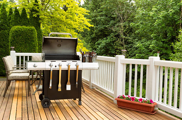 BBQ cooker and cookware ready to cook Photo of a clean barbecue cooker with cookware and cold beer in bucket on cedar wood patio. Table and colorful trees in background. barbecue grill stock pictures, royalty-free photos & images
