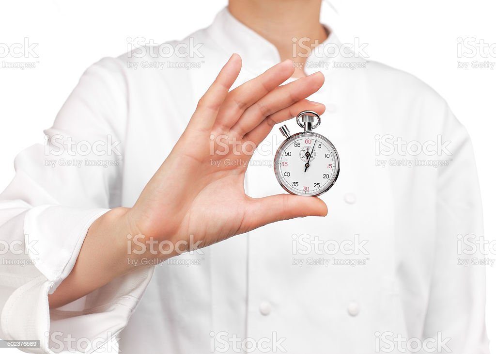 cooker holding a stopwatch stock photo
