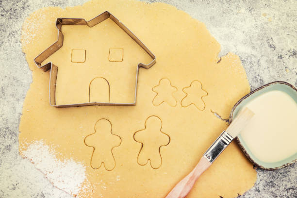 Cookie dough and cutter, family and house cutout, concept planning and baking a family Cookie dough and cutter, family and house cutout, concept planning and baking a family cookie cutter stock pictures, royalty-free photos & images