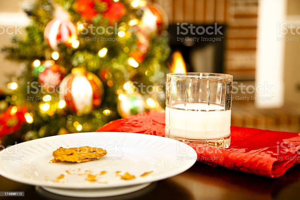 Cookies and milk sampled by Santa near Christmas tree stock photo