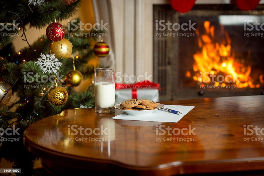 Cookies, glass of milk and letter for Santa on table stock photo