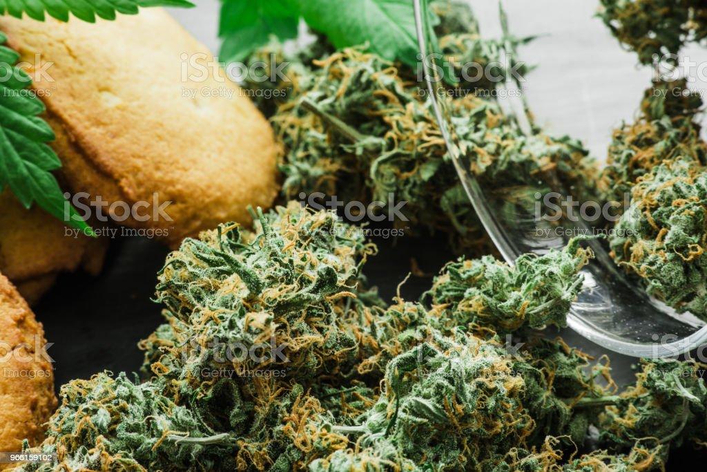 Cookies med cannabis och knoppar av marijuana på bordet. En burk med cannabis knoppar begreppet matlagning med cannabisblad. Behandling av medicinsk marijuana för användning i livsmedel, på en svart bakgrund - Royaltyfri Choklad Bildbanksbilder