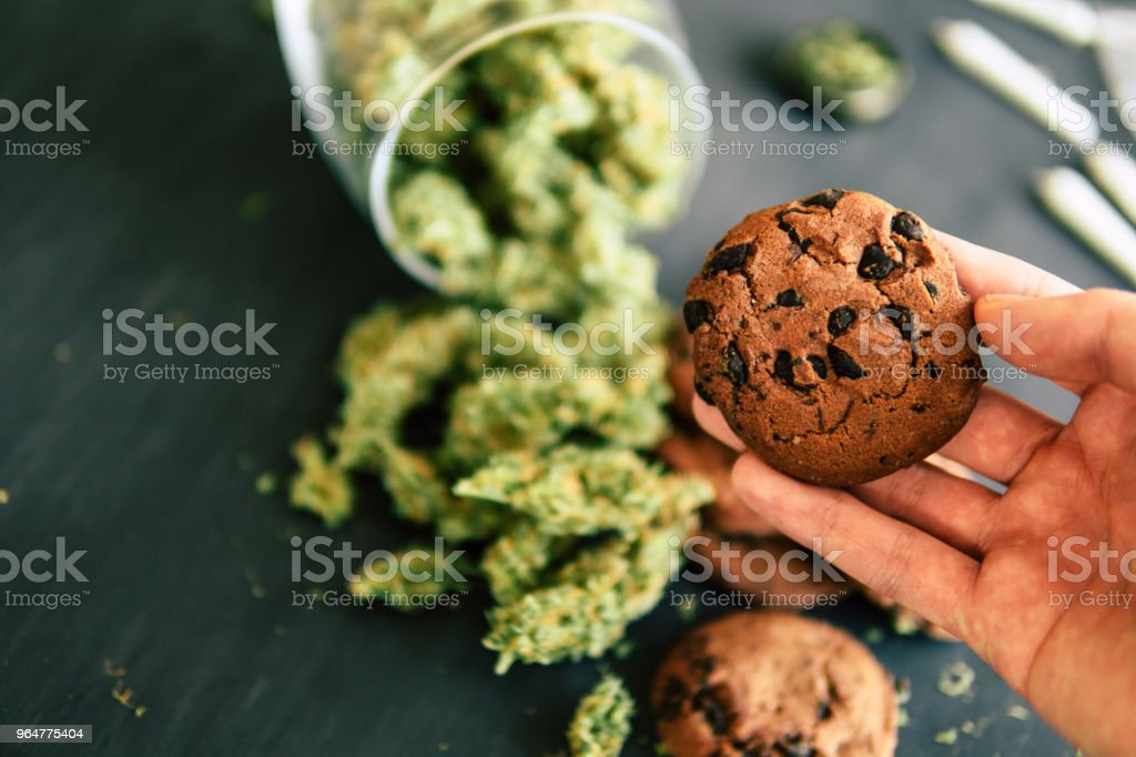 Cookies with cannabis and buds of marijuana on the table. Concept of cooking with cannabis herb. Treatment of medical marijuana for use in food, On a black background top view royalty-free stock photo