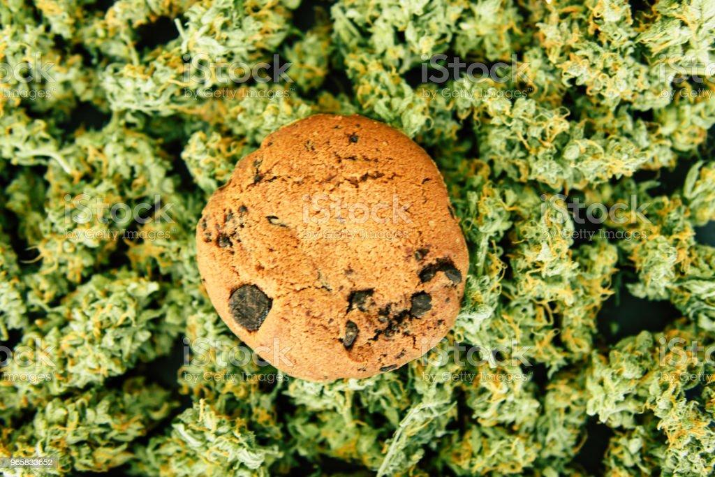 Koekjes met cannabis en toppen van marihuana op de tafel. Concept van het koken met cannabis kruid. Behandeling van medische marihuana voor gebruik in levensmiddelen, op een zwarte achtergrond - Royalty-free Blad Stockfoto