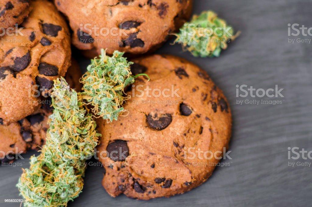 Koekjes met cannabis en toppen van marihuana op de tafel. - Royalty-free Biologisch Stockfoto