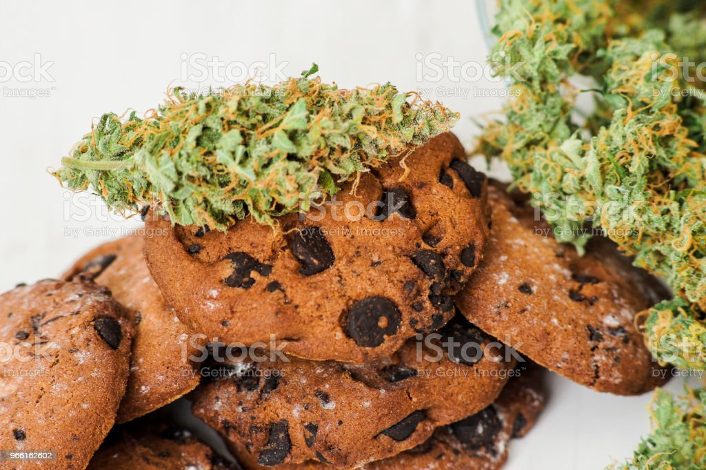 Cookies med cannabis och knoppar av marijuana på bordet. - Royaltyfri Choklad Bildbanksbilder