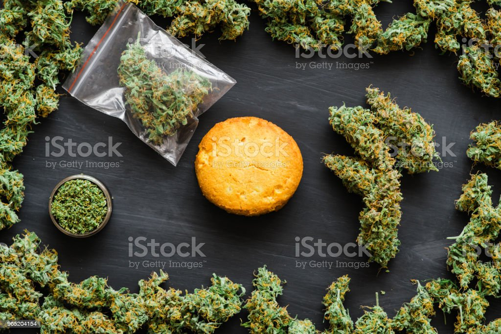 Cookies with CBD and fresh green buds of cannabis in hand Joint in hand A lot of marijuana Package with weed and fresh buds of cannabis many weed. Copy spase Copy-space royalty-free stock photo