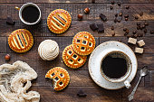 Cookies with jam and coffee on rustic wooden table. Top view