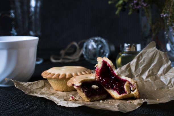 kekse mit marmelade auf braunem papier auf schwarzen backgroung - aufstrich weihnachten stock-fotos und bilder