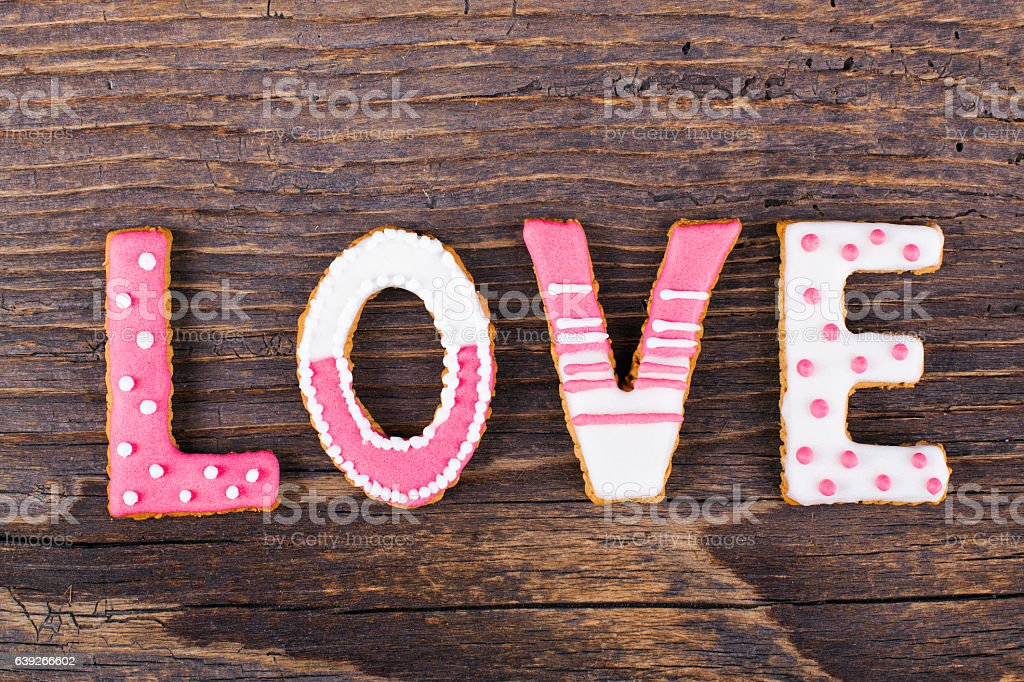 Cookies with love text in plate on rustic wooden table. 스톡 사진