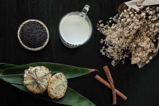 cookies with sesame seeds and glass of milk, homemade sweet cookies stock photo
