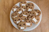 Home made cookies on white plate with face protective mask on wooden background.