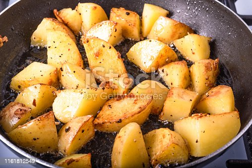 Cooking a rustic breakfast - large pieces of potatoes are fried in a pan