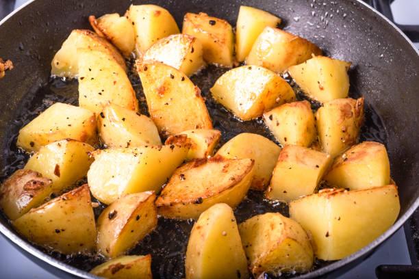 Cozinhando um pequeno almoço rústico-as grandes partes de batatas são fritadas em uma bandeja - foto de acervo