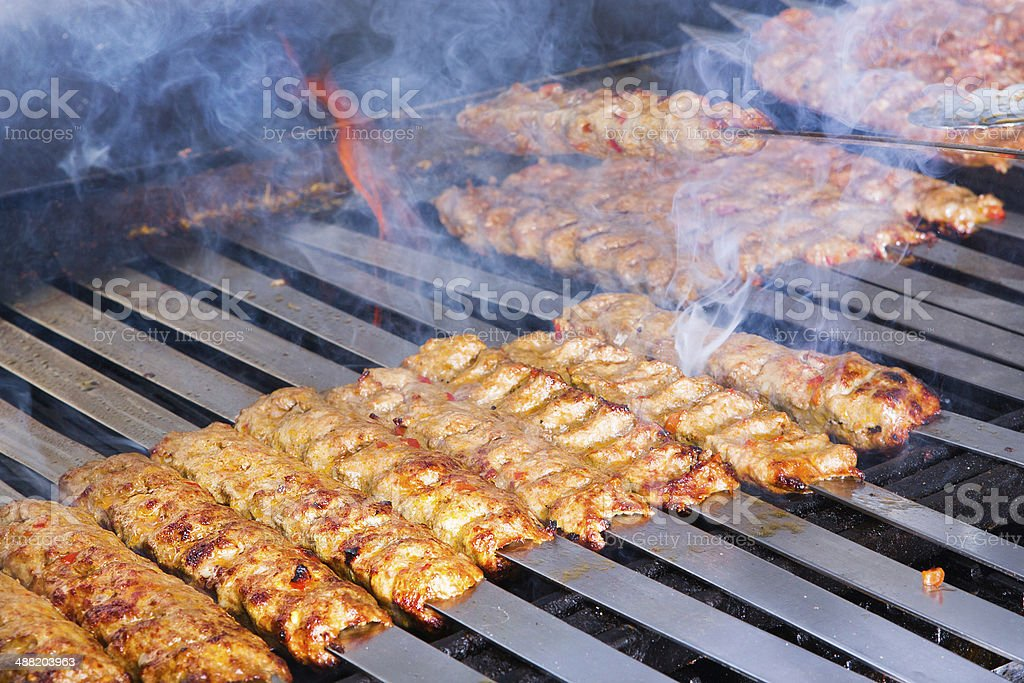 Cooking Adana Lamb Kebabs on the Restaurant Style Grill stock photo