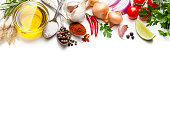 Cooking and seasoning backgrounds: High angle view of a white background with multi colored vegetables, herbs and spices placed at the top border making a frame and leaving a useful copy space for text and/or logo at the center. The composition includes olive oil, cherry tomatoes, lime slice, red onion, parsley, star anise, garlic, salt, pepper, chili pepper, and gold onions. High key DSRL studio photo taken with Canon EOS 5D Mk II and Canon EF 100mm f/2.8L Macro IS USM.