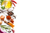 Cooking and seasoning backgrounds: High angle view of a white background with multi colored vegetables, herbs and spices placed at the left border making a frame and leaving a useful copy space for text and/or logo at the center. The composition includes olive oil, cherry tomatoes, lime slice, red onion, parsley, star anise, garlic, salt, pepper, chili pepper, turmeric and gold onions. High key DSRL studio photo taken with Canon EOS 5D Mk II and Canon EF 100mm f/2.8L Macro IS USM.