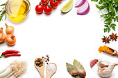 Cooking and seasoning backgrounds: High angle view of a white background with multi colored vegetables, herbs and spices placed all around the border making a frame and leaving a useful copy space for text and/or logo at the center. The composition includes olive oil, cherry tomatoes, lime slice, red onion, parsley, star anise, curry powder, garlic, bay leaves, nutmeg, salt, pepper, chili pepper, and gold onions. High key DSRL studio photo taken with Canon EOS 5D Mk II and Canon EF 100mm f/2.8L Macro IS USM.