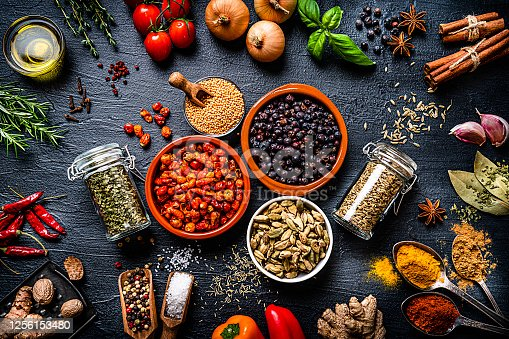 Cooking and seasoning backgrounds: large group of multicolored ingredients, spices and vegetables shot from above on black stone background. The composition includes spices like mustard seeds, paprika, turmeric, pepper, cinnamon sticks, star anise, cardamom, nutmeg, bay leaves, dried oregano and vegetables like onion, garlic, peppers, olive oil, rosemary, basil, dried tomatoes, cherry tomatoes, cucumber among others. A cutting board with vegetables and a cast iron pan complete the composition. High resolution 42Mp studio digital capture taken with SONY A7rII and Zeiss Batis 40mm F2.0 CF lens