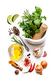 Cooking and seasoning ingredients: High angle view of multi colored vegetables, herbs and spices shot on white background. The composition includes olive oil, lime slices, rosemary, parsley, curry powder, garlic, nutmeg, paprika, pepper, chili pepper and gold onions. A white mortar filled with fresh herbs is at the top right of a vertical frame. High key DSRL studio photo taken with Canon EOS 5D Mk II and Canon EF 100mm f/2.8L Macro IS USM.