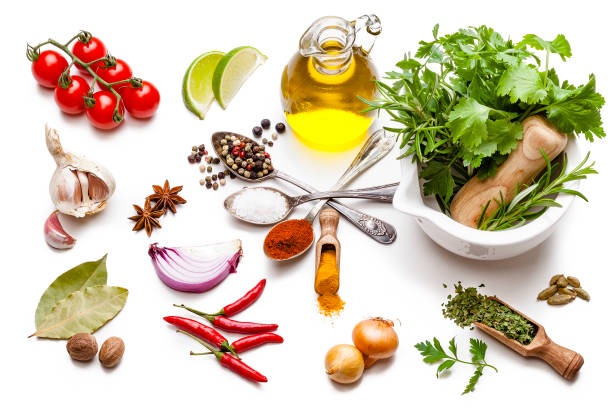 Cooking and seasoning ingredients: vegetables, herbs and spices on white background. Cooking and seasoning backgrounds: High angle view of multi colored vegetables, herbs and spices shot on white background. The composition includes olive oil, cherry tomatoes, lime slice, red onion, cardamom, rosemary, parsley, star anise, curry powder, garlic, bay leaves, nutmeg, salt, paprika, pepper, chili pepper, and gold onions. High key DSRL studio photo taken with Canon EOS 5D Mk II and Canon EF 100mm f/2.8L Macro IS USM. star anise on white stock pictures, royalty-free photos & images