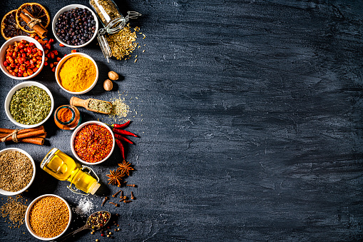 Cooking and seasoning backgrounds: group of multicolored ingredients, spices and vegetables arranged at the left border of a black background shot from above making a frame and leaving useful copy space for text and/or logo. The composition includes spices like paprika, turmeric, pepper, dried oregano, cinnamon, star anise, nutmeg, chili pepper, olive oil, clove, among others. High resolution 42Mp studio digital capture taken with SONY A7rII and Zeiss Batis 40mm F2.0 CF lens