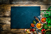 istock Cooking background: multi colored spices, herbs and vegetables on rustic wooden table. Copy space 1272783747