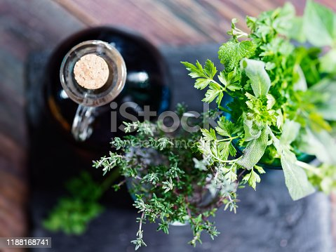 Cooking background with fresh herbs and red vinegar